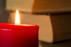 Den brinnande stearinljuset mot böcker Fotografering för Bildbyråer
