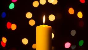 Den brinnande stearinljuset mot ferie tänder bakgrund Fotografering för Bildbyråer
