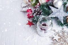 Den brinnande stearinljuset och julgarnering över snö och träbakgrund, den eleganta låg-tangenten sköt med festligt lynne royaltyfri fotografi