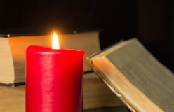 Den brinnande stearinljuset och några gamla böcker Royaltyfri Foto