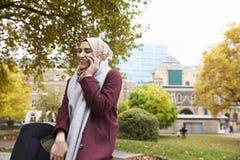 Den brittiska muslimska kvinnan på avbrottet som använder mobiltelefonen parkerar in Arkivbilder