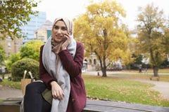 Den brittiska muslimska kvinnan på avbrottet som använder mobiltelefonen parkerar in Royaltyfri Bild