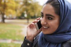 Den brittiska muslimska kvinnan som använder mobiltelefonen parkerar in Royaltyfria Bilder