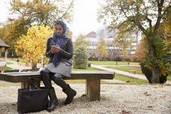 Den brittiska muslimska kvinnan som smsar på mobiltelefonen parkerar in Royaltyfria Bilder