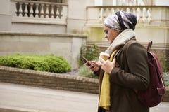 Den brittiska muslimska kvinnlign går och överför textmeddelandet i stad Royaltyfri Fotografi