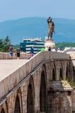 Den broarkitekturen och jätten brons statyn av den forntida krigarekonungen, Philip Second av Macedon, den fadern av Alexander arkivfoto