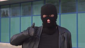 Den brottsliga den mantjuven eller rånaren i maskering visar upp tummen stock video