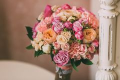 Den brud- buketten med rosa rosor och persikapioner står på bakgrund av tappningväggen Royaltyfria Bilder