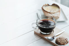 Den Brulee kokosnötkrämen är söta anstrykningar och drinken med svart kaffe för varm americano på vit trätabellbakgrund arkivbild