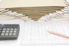 Den bruna blyertspennan med räknemaskinen har kuvertet mellan skrivbordsarbete som bakgrund Arkivfoton