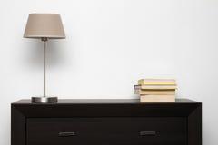 Bryna commoden med lampan och bokar i minimalisminre arkivbilder