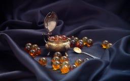 Den bruna genomskinliga naturliga gemstonerundan pryder med pärlor att ligga i ett antikt saltkar med en sked royaltyfri foto