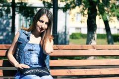 Den bruna haired unga kvinnan sitter på en bänk Arkivfoton