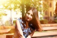 Den bruna haired unga kvinnan sitter på en bänk Arkivbilder