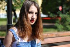 Den bruna haired unga kvinnan sitter på en bänk Arkivbild