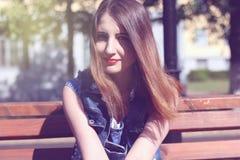 Den bruna haired unga kvinnan sitter på en bänk Royaltyfri Foto
