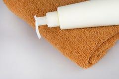 Den bruna handduken och duschen stelnar på en grå bakgrund framsidakräm och handduk på tabellen Skönhetsmedel SPA som brännmärker arkivfoton