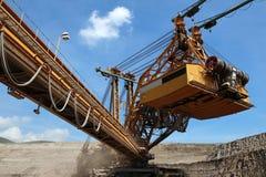 den bruna kolgrävskopamaskinen bryter Arkivbilder