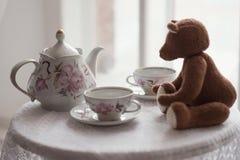Den bruna leksakbjörnen sitter på en tabell med två koppar för te och en kokkärl royaltyfri bild
