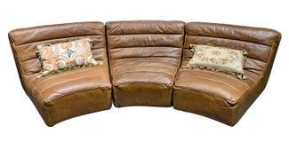 Den bruna modulläderhalv-cirkuläret soffan med gobelängkudden isolerade vit bakgrund Fotografering för Bildbyråer