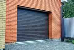 Den bruna porten i ett privat garage och delen av ett järn fäktar Royaltyfria Foton