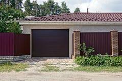 Den bruna porten i ett privat garage och ett järn fäktar nära vägen Arkivfoton