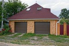 Den bruna porten i ett privat garage och ett järn fäktar nära vägen i gräset Royaltyfria Bilder