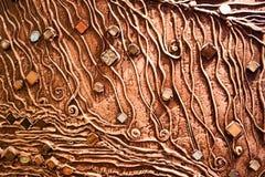 Den bruna texturen av betongväggen göras av dekorativ murbruk med tillägget av mång--färgad ädelstenar, exponeringsglasfyrkanter  Royaltyfri Fotografi