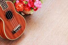 Den bruna ukulelet lägger på den gamla bruna Wood tabellen Royaltyfri Foto