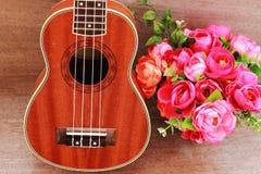 Den bruna ukulelet lägger på den gamla bruna Wood tabellen Royaltyfria Foton
