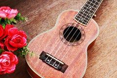 Den bruna ukulelet lägger på den gamla bruna Wood tabellen Arkivfoto