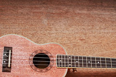 Den bruna ukulelet lägger på den gamla bruna Wood tabellen Arkivfoton