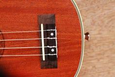 Den bruna ukulelet lägger på den gamla bruna Wood tabellen Arkivbild
