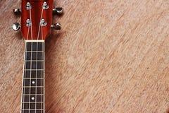 Den bruna ukulelet lägger på den gamla bruna Wood tabellen Arkivbilder