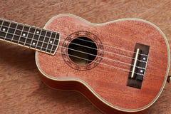 Den bruna ukulelet lägger på den gamla bruna Wood tabellen Royaltyfria Bilder