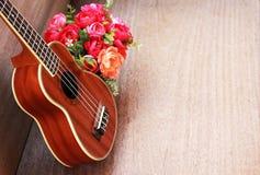 Den bruna ukulelet lägger på den gamla bruna Wood tabellen Fotografering för Bildbyråer