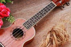 Den bruna ukulelet lägger på den gamla bruna Wood tabellen Royaltyfri Bild