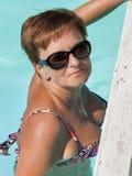 Den brunbrända caucasian mitt åldrades kvinnan som ser från den utomhus- pölen Fotografering för Bildbyråer