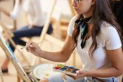 Den brunhåriga flickan i exponeringsglas iklädd vit t-skjorta och jeans med en halsduk runt om hennes hals målar en bild i konste arkivbilder