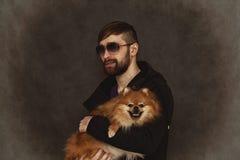 Den brutala grabben grinar i solglasögon, med ett skägg och en innegrejfrisyr och innehav en hund arkivbilder