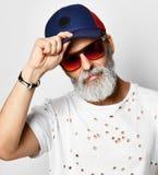 Den brutala höga rikeman i märkes- t-skjorta rymmer skärmen av hans stilfulla trendiga män för den blåa och röda baseballmössan royaltyfri foto