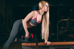 Den brutala idrotts- kvinnan som pumpar upp, tränga sig in med hantlar i idrottshall arkivbild