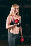 Den brutala idrotts- kvinnan som pumpar upp, tränga sig in med hantlar i idrottshall fotografering för bildbyråer