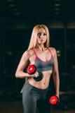 Den brutala idrotts- kvinnan som pumpar upp, tränga sig in med hantlar i idrottshall royaltyfria foton