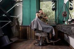 Den brutala mannen med thaskägget sitter i stolen, framme som spegeln på en barberare shoppar Barberarerakningar mans hår arkivbilder