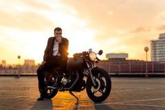 Den brutala mannen sitter på mopeden för kaféracerbilegenn Arkivfoto
