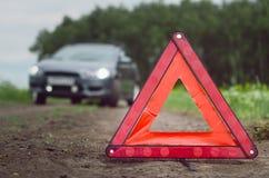 Den brutna bilen på nöd- stopp för vägren och för röd triangel undertecknar royaltyfri fotografi