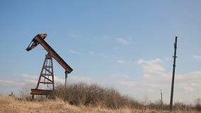 Den brutna och övergav olje- pumpen på en bakgrund av blå himmel och vit fördunklar lager videofilmer
