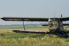 Den brutna sovjetiska biplanen står på ett övergett flygfält royaltyfria bilder