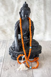 Den Buddah statyn med apelsinen pryder med pärlor för läs- mantras Arkivbild